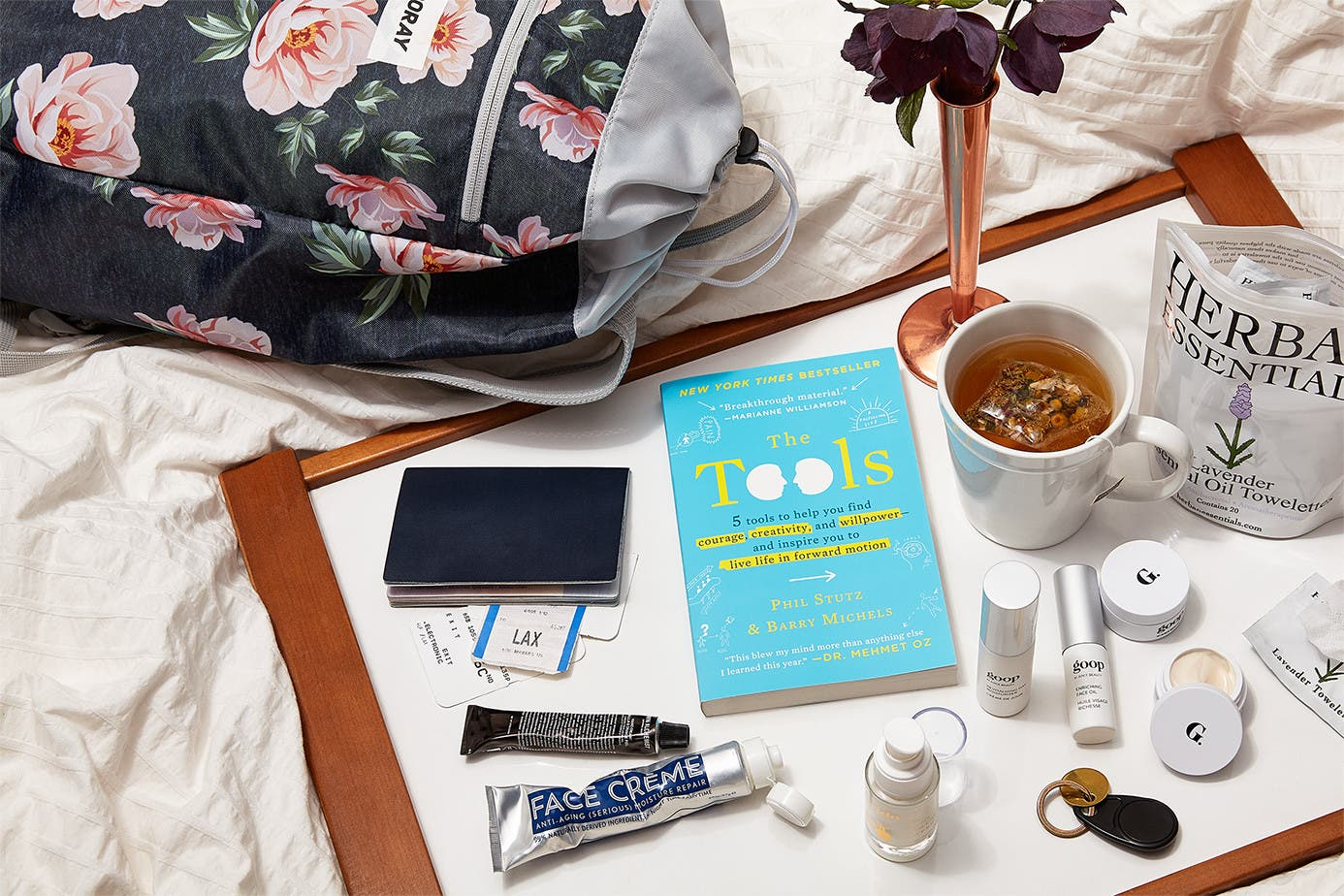 goop travel products sprawled out on a bed sheet.