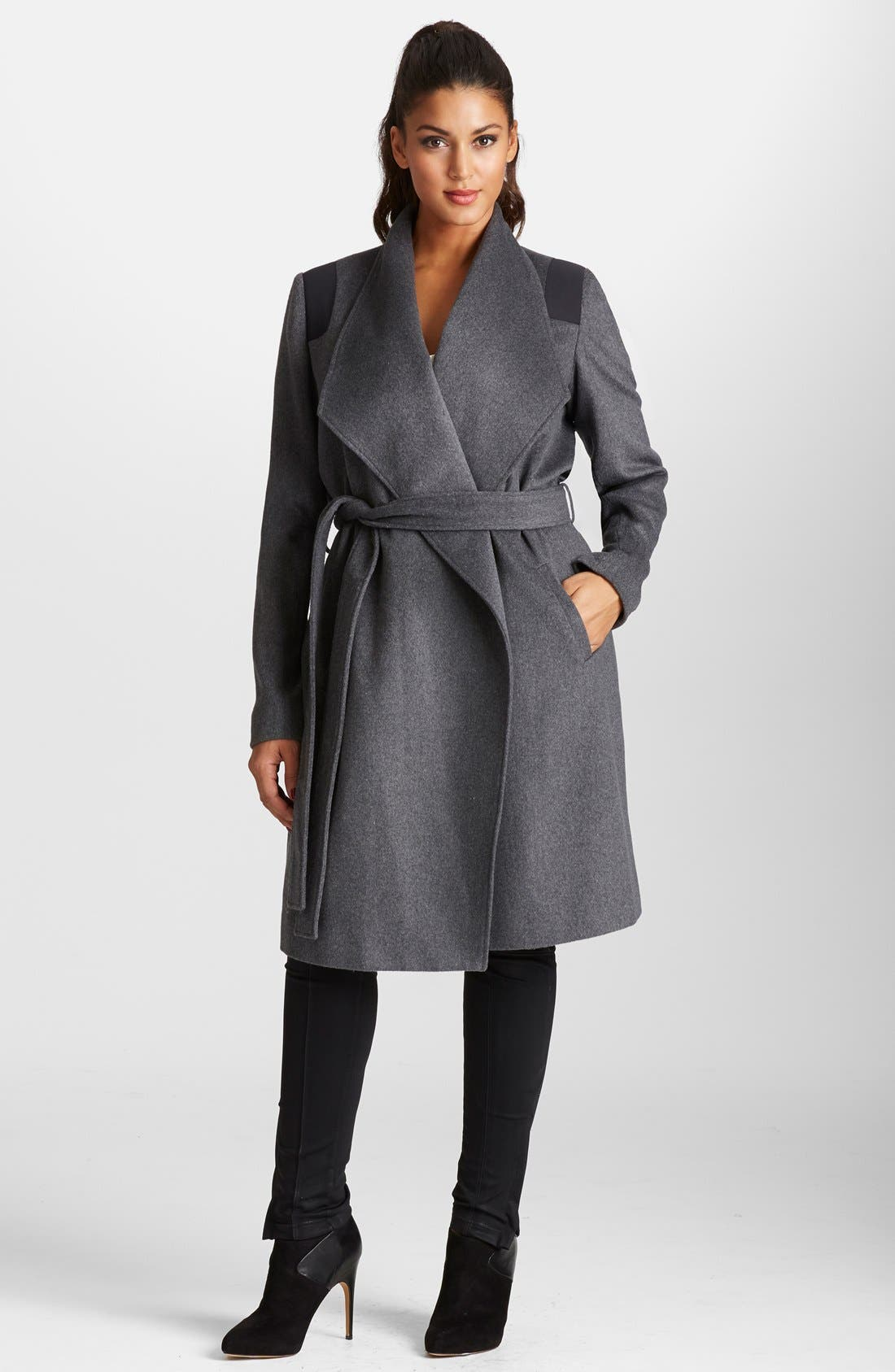 The coat is a smooth wool, and I am sure if would be a good idea to keep a lint brush on hand - but that's with all black wool coats. The neck line is gorgeous. Great buy.