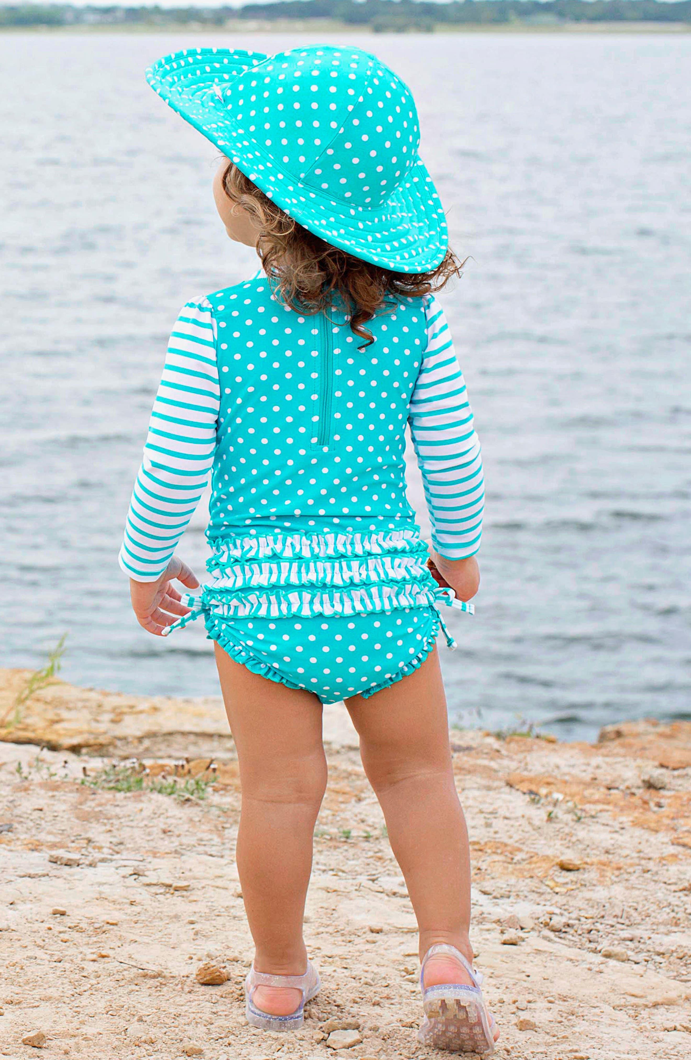 Alternate Image 4  - RuffleButts One-Piece Rashguard Swimsuit & Hat Set (Baby Girls)