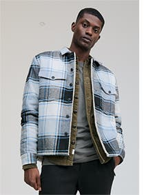 Model in a checkered blue and black shirt jacket.