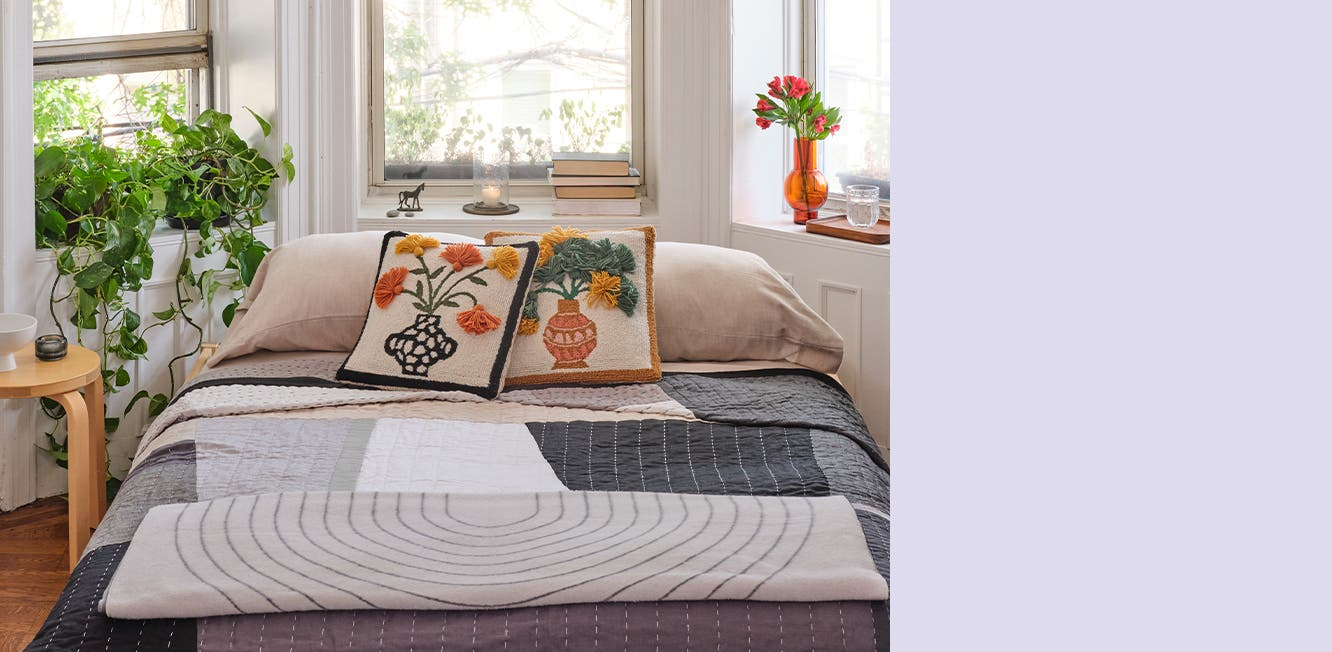 Bedding in shades of gray plus floral throw pillows.
