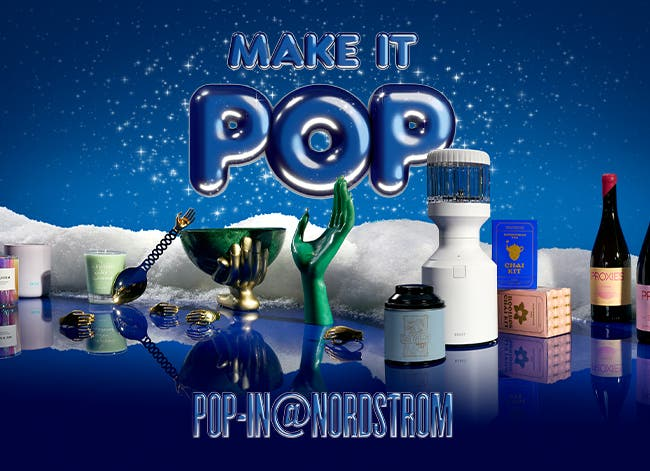Make It Pop-In@Nordstrom. A selection of gifts in the snow including a hand-shaped candle, scented candle, sleek blender; a green bowl and serving spoon adorned with a golden hand; chai tea kits; and bottles of non-alcoholic wine.