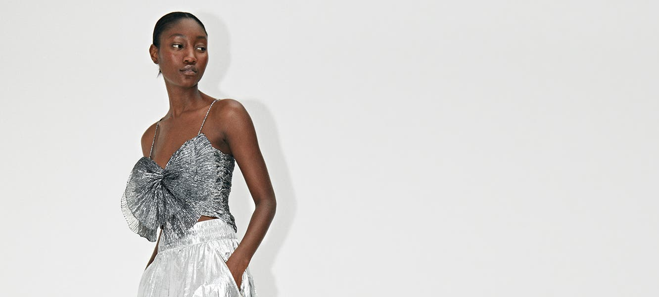 A woman in a silver top with bow detail and pants by Isabel Marant.