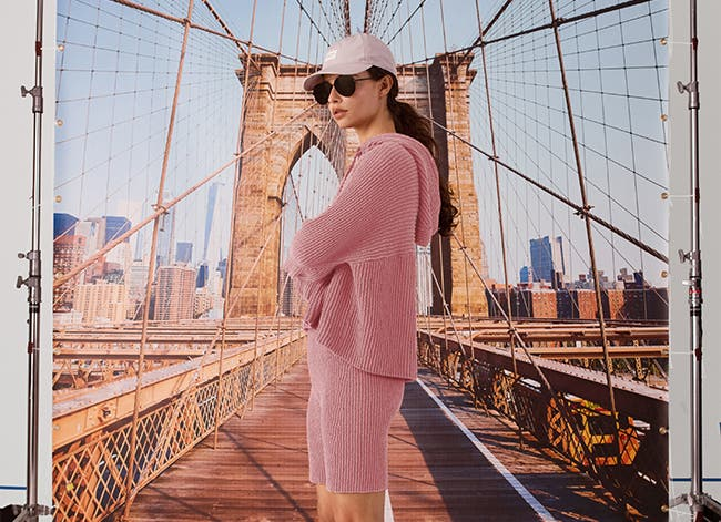Rag & bone summer collection: woman wearing a pink hooded sweater with matching biker shorts, cap and sunglasses.