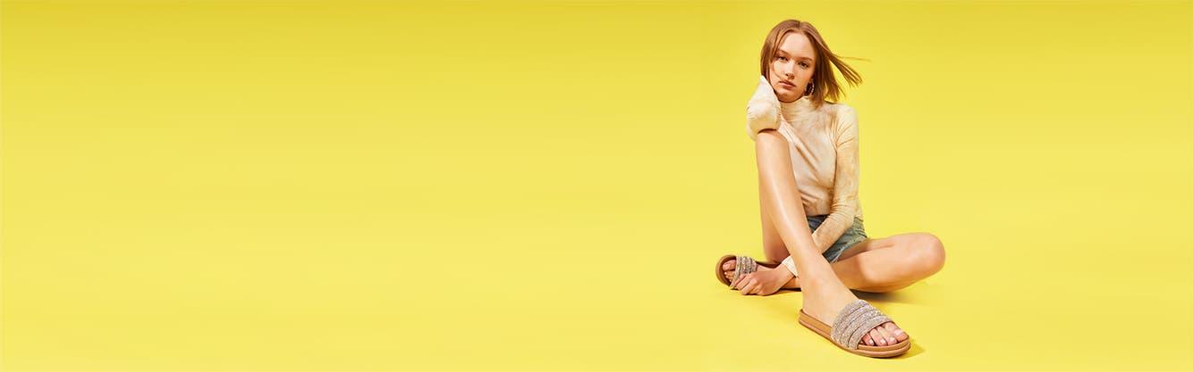 A young woman wearing Steve Madden slide sandals.