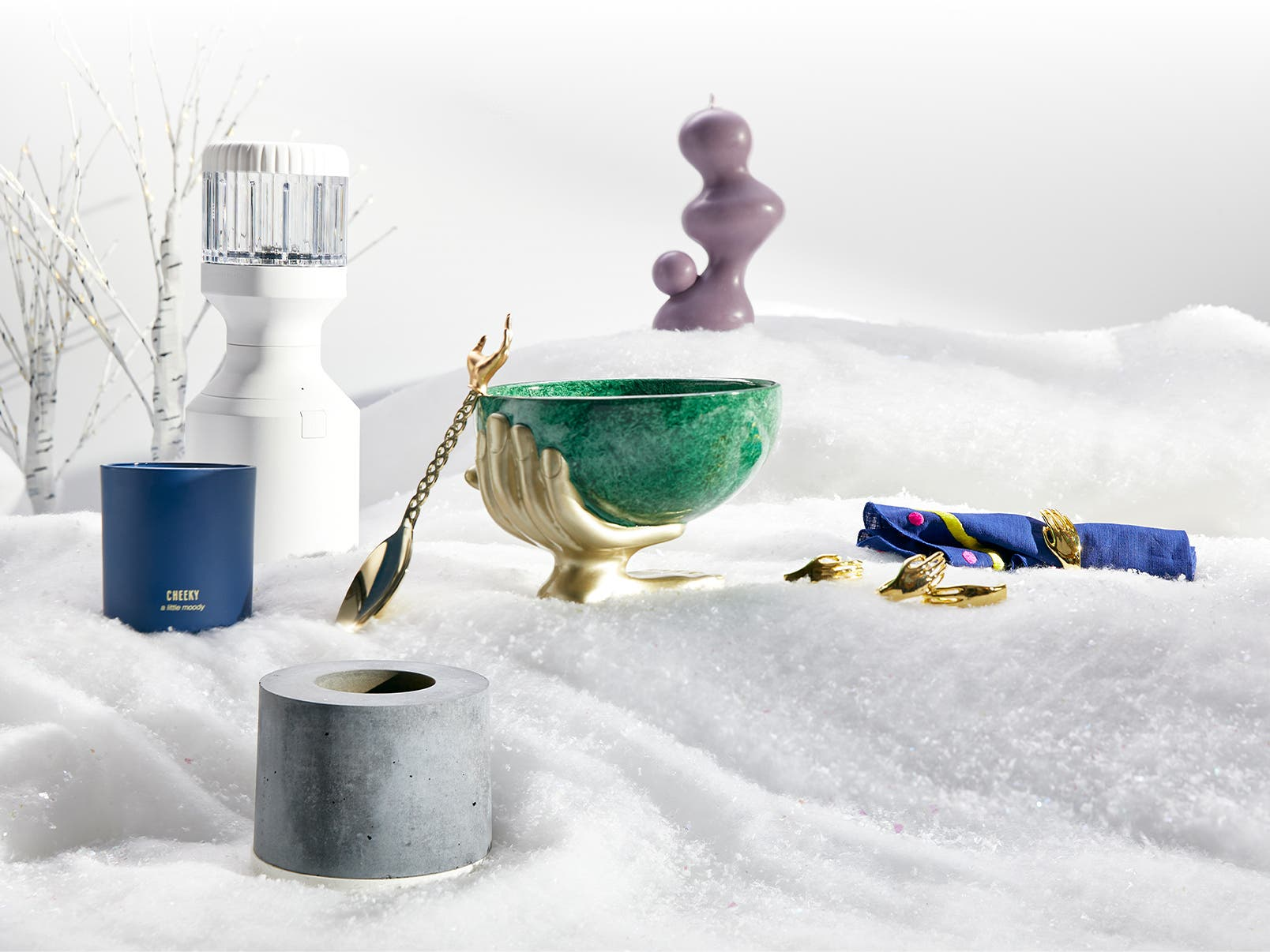 Hashtag Nordstrom Pop. A selection of gifts in the snow including a purple sculptural candle, scented candle, sleek blender; and a green bowl and serving spoon adorned with a golden hand.