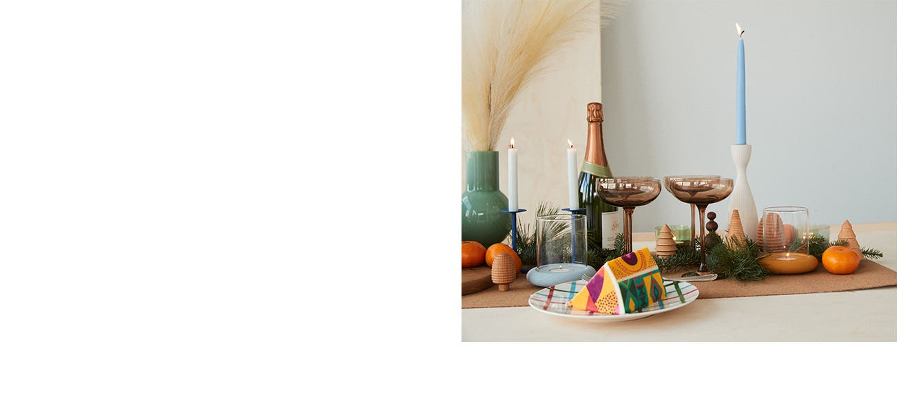 A table setting with candles, glassware, cake and fruit, greenery and wooden Christmas trees.