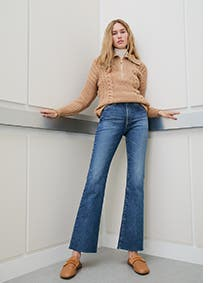 Woman wearing a tan sweater with jeans and tan mules.