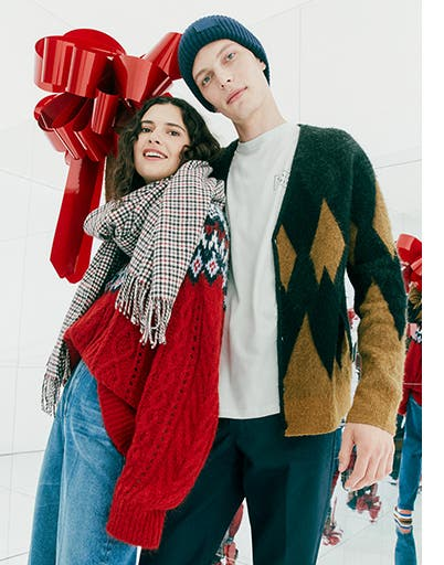 A woman wearing a sweater and scarf. A man wearing a cardigan and beanie.