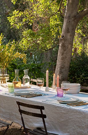 An outdoor dining table set with glasses, plates and more dinnerware.