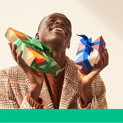 Gifts for him under $50: a man holding two presents.