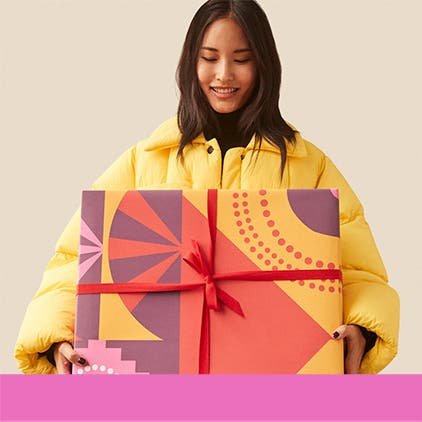 Gifts for her under $100: woman in a yellow coat holding a gift.
