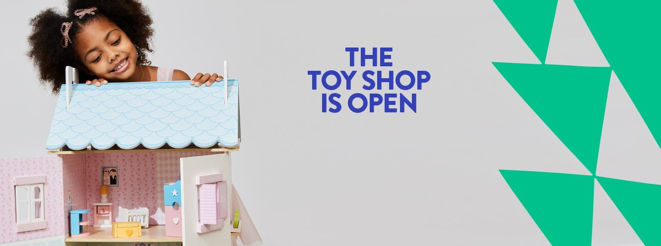 The toy shop is open. A smiling little girl peering over the top of a dollhouse.