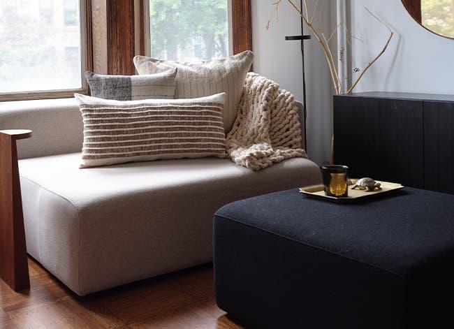 A modern sofa with cozy pillows and a chunky throw.