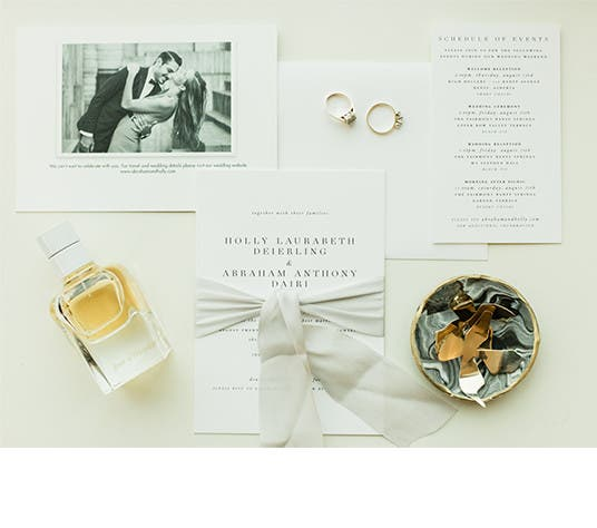 Wedding items, including the invitation and their rings, for bride and groom Holly and Abraham.