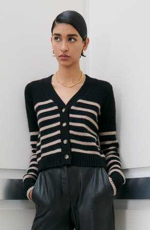 A woman wearing a striped cardigan with black pants.