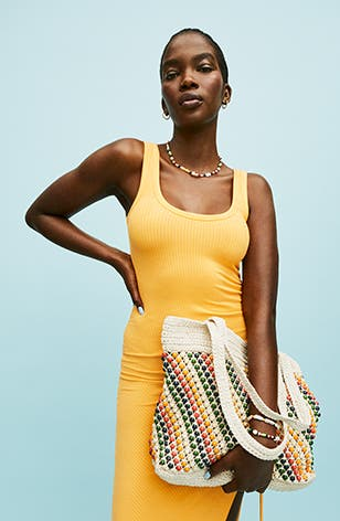 Woman wearing a yellow dress and holding a multicolored woven bag.