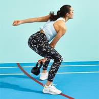 Woman swinging a kettlebell wearing Sweaty Betty leggings and tank top.