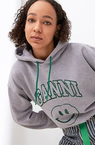 Woman in a grey smiley-face Ganni sweatshirt and a pair of striped pants.