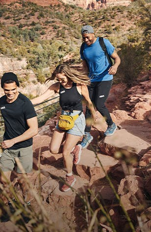 A woman and two men hike in HOKA gear.