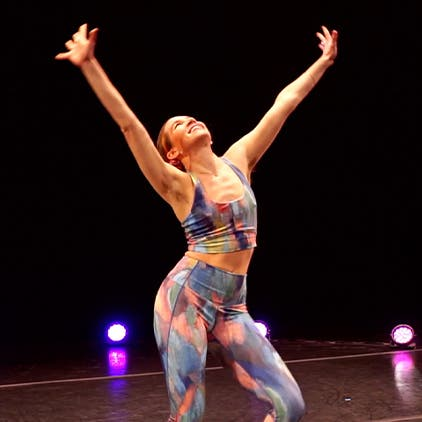 Woman dancing on a stage in activewear.