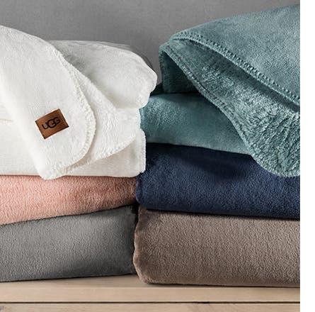 Stacks of UGG blankets.