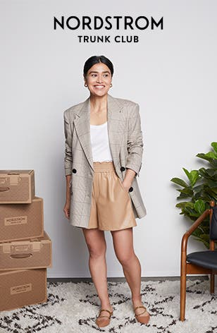 A woman next to a stack of Nordstrom Trunk Club Trunks wearing a blazer, a tank top, shorts and flats.