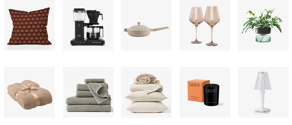 A red patterned accent pillow; a Moccamaster coffee brewer; an Always pan from Our Place; a pair of wineglasses; a houseplant in a vase; a throw blanket folded and tied with a ribbon; a stack of matching bath towels, hand towels and washcloths; a sheet set; a candle and the box it comes in; a table lamp.
