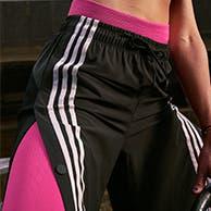 Close-up of a woman wearing striped adidas pants.