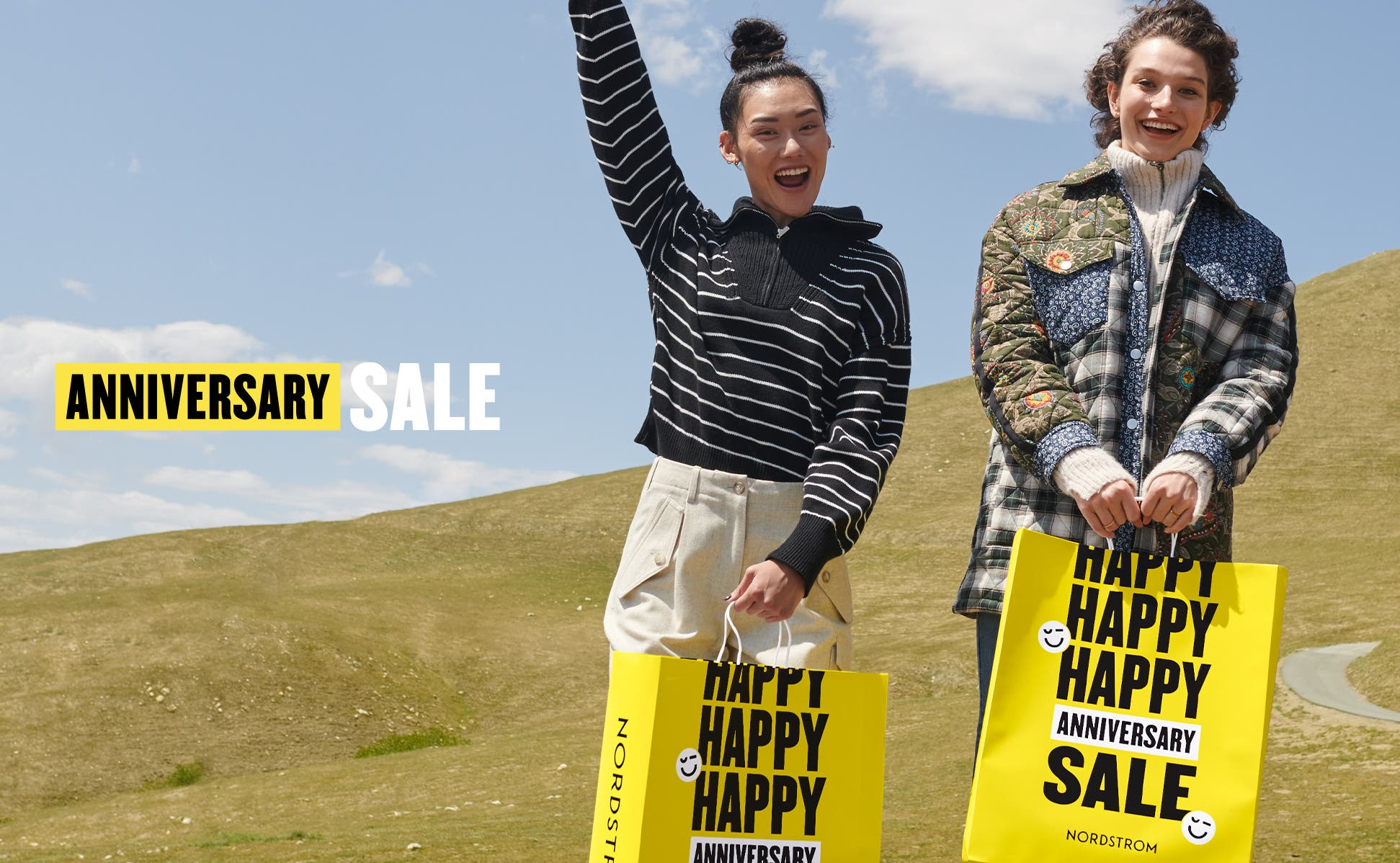 Two people jumping in a field with Anniversary Sale shopping bags.