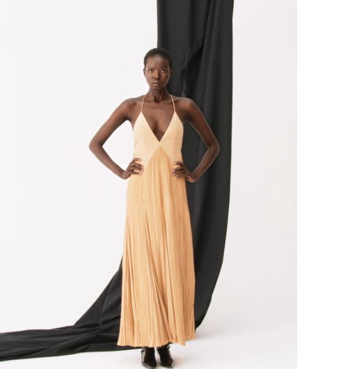 Woman wearing a strappy pleated dress from Khaite.