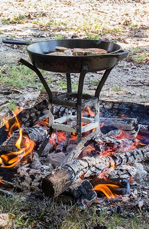 A cast iron skillet cooking steaks over a campfire.