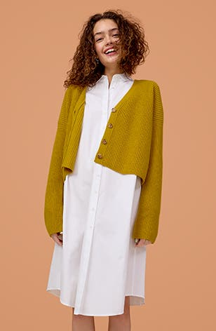 Woman wearing a white shirtdress and yellow cardigan.