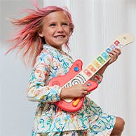 A girl playing a toy guitar.
