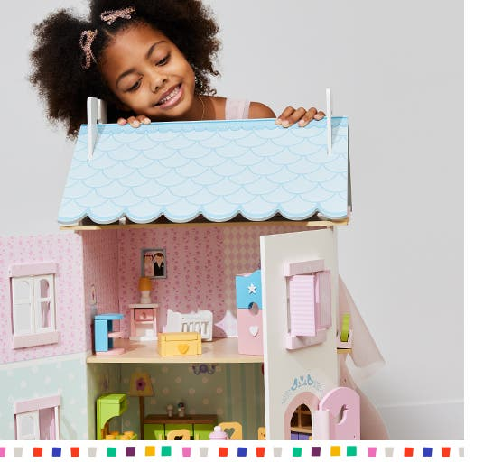 A smiling little girl peering over the top of a dollhouse.