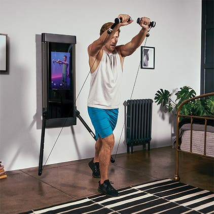 Man working out with Tonal home gym equipment.