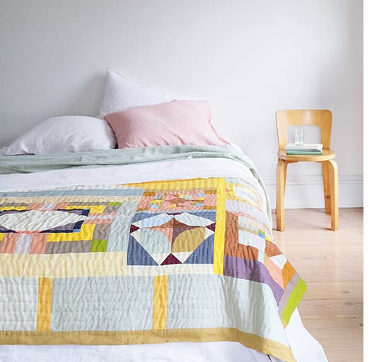 A bed with a patchwork quilt and a chair stacked with books.