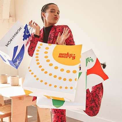 Gift and style help: a woman holding Nordstrom holiday shopping bags.