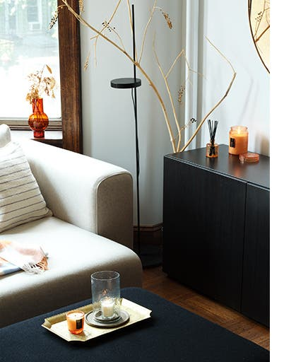 A living room decorated with candles and a reed diffuser.