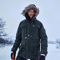 A man wearing a parka in the snow.