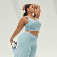 Woman stretching in light-blue matching Zella leggings and sports bra.