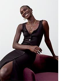 Woman wearing a black button-up tank dress.