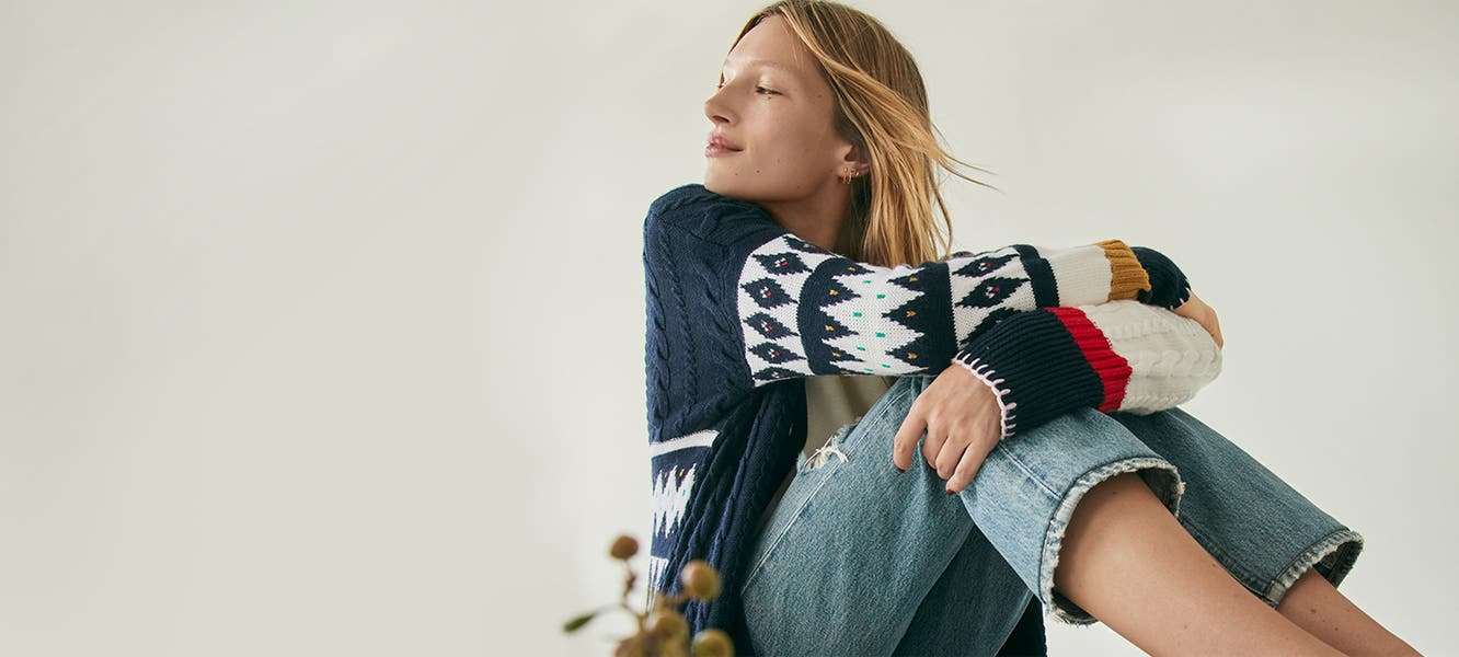 A woman wearing a patterned cardigan and faded cropped jeans.