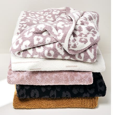A stack of Barefoot Dreams throw blankets.