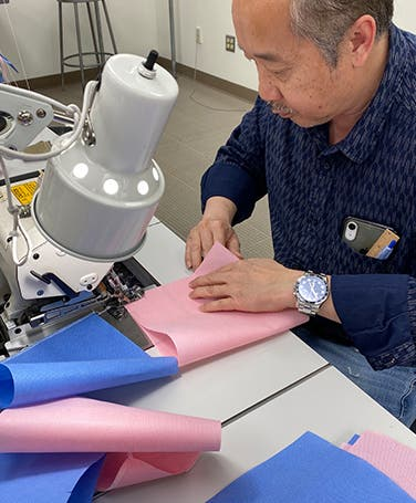 Nordstrom tailor sewing a COVID-19 mask.