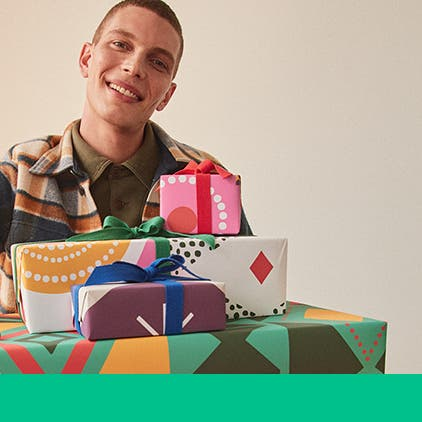 Gifts for him under $50. A man holding a stack of wrapped gifts.