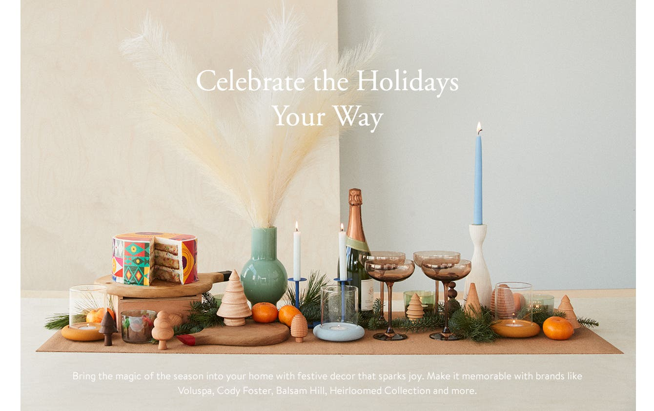 Celebrate the Holidays Your Way. Bring the magic of the season into your home with festive decor that sparks joy. Make it memorable with brands like Voluspa, Cody Foster, Balsam Hill, Heirloomed Collection and more. A table setting with candles, glassware, cake and fruit, greenery and wooden Christmas trees.