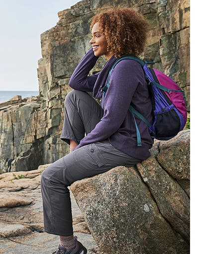 A woman in activewear sitting on a boulder.