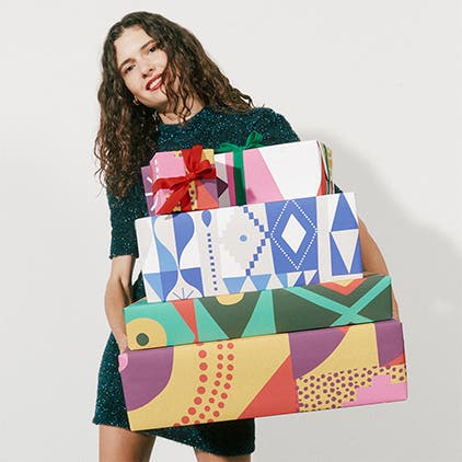 Gift wrapping: a women with a stack of wrapped gifts.