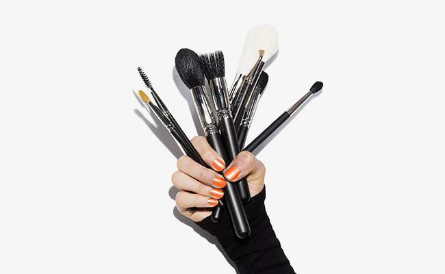 A beauty stylist holding makeup brushes